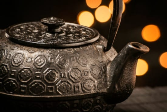 Closeup of a black, cast-iron teapot on a black bamboo mat